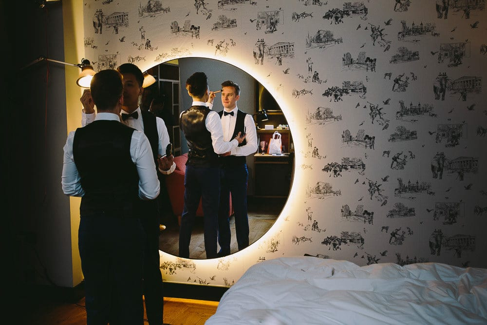 Both grooms reflections in the large mirror