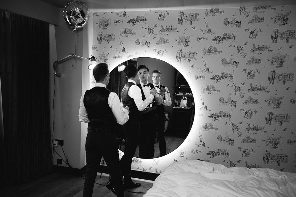 Both grooms reflections in a large mirror at The Hoxton London