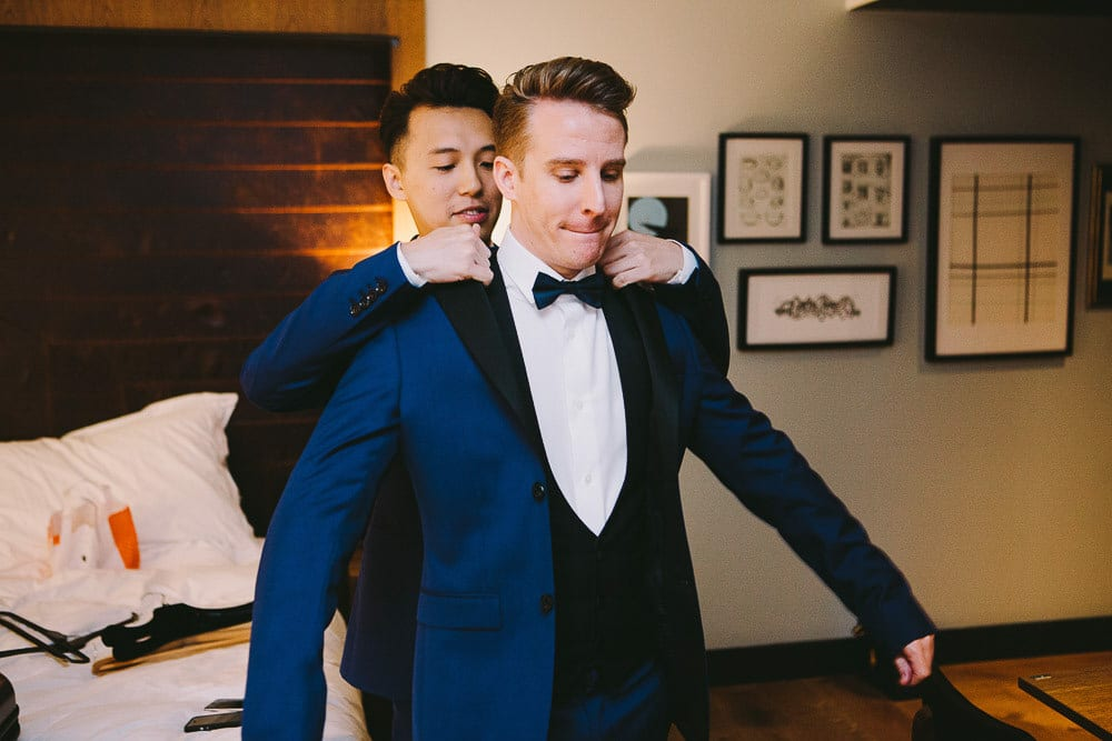 Grooms putting on their suit jackets in the hotel room at The Hoxton London