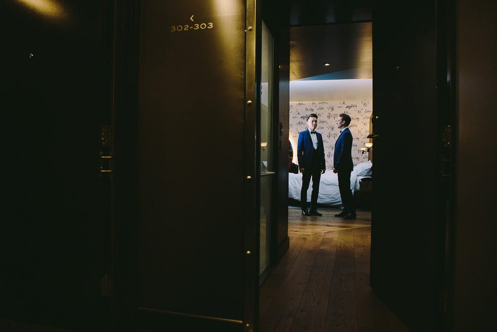 Both grooms stood in their hotel room taken from the hallway at The Hoxton London