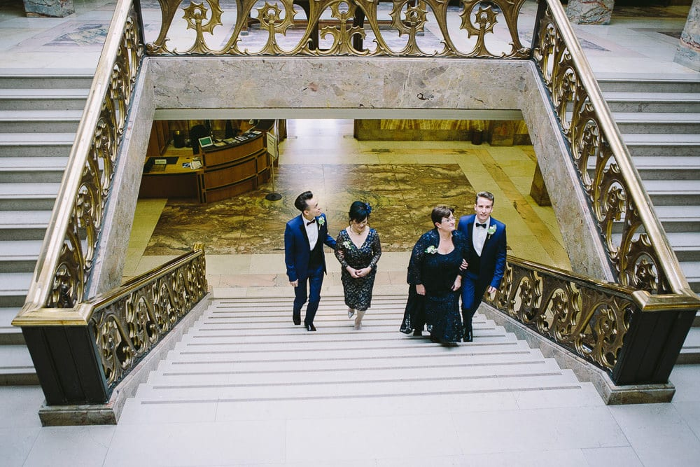 Both grooms walking up the marble staircase with both mothers at Wandsworth Town Hall