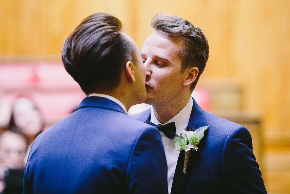 Grooms sharing a kiss after the ceremony in the Grand Chamber