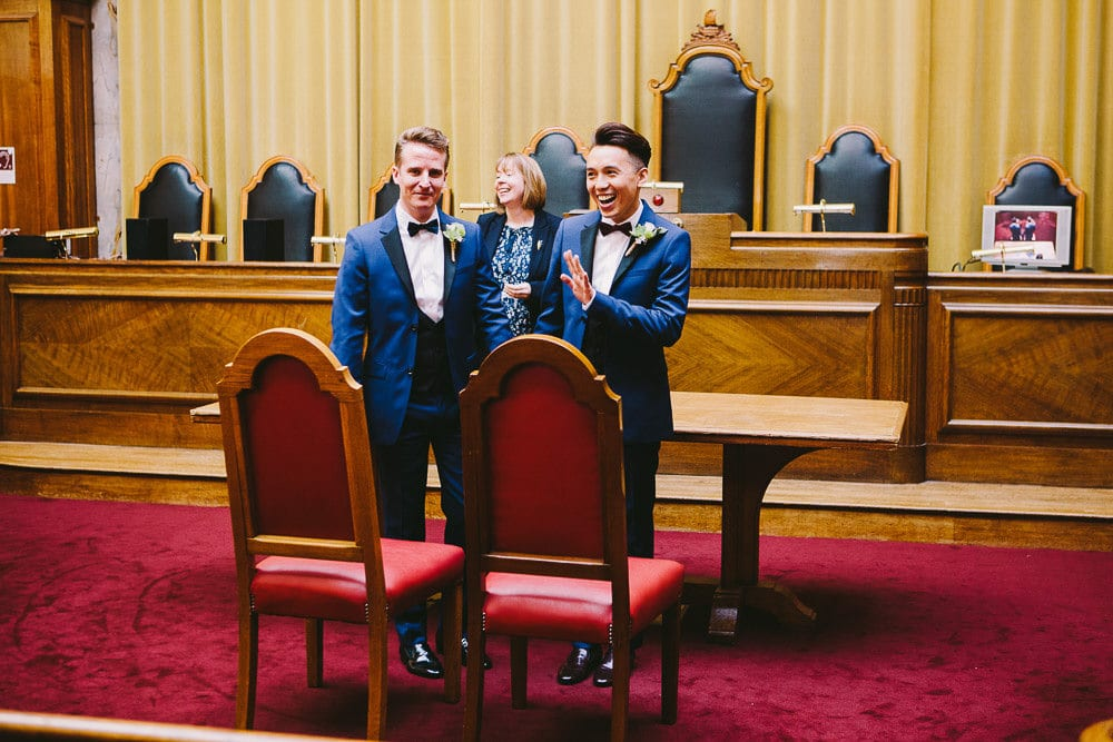Both grooms smiling at their friends and family after getting married