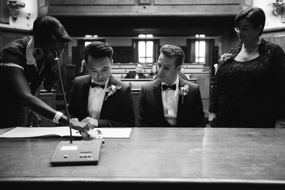Black and white image of grooms signing the register at Wandsworth Town Hall