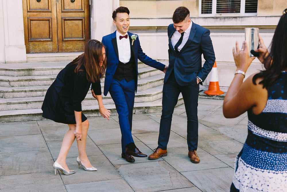 Groom and guests messing about outside Wandsworth Town Hall