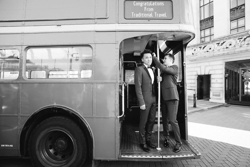 Grooms standing at the rear of vintage bus outsdie Wandsworth Town Hall