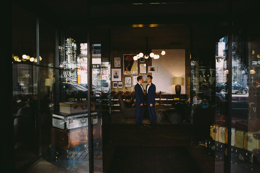 Grooms holding hand in the lobby of The Hoxton London