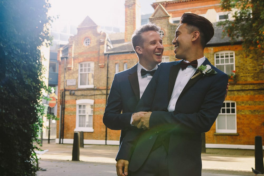 Portrait of grooms laughing outside The Hoxton London