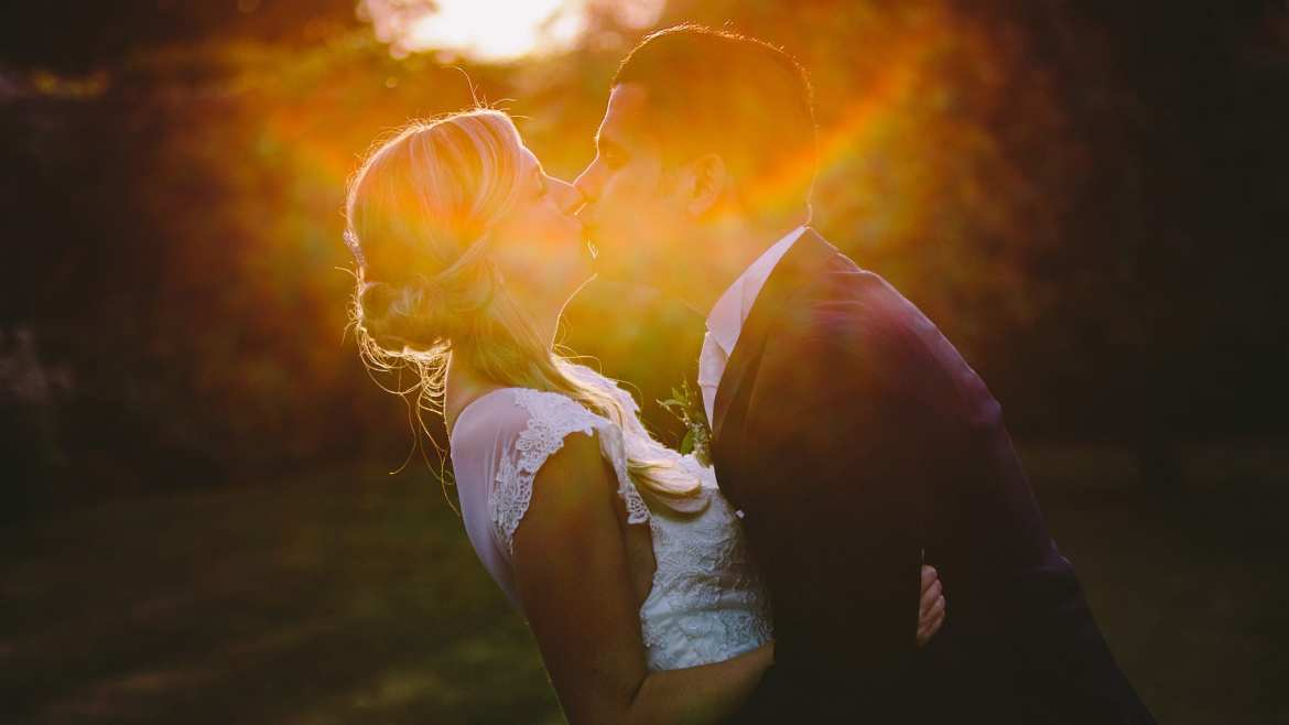 Bride and groom kiss in the sunset at Rockley Manor, Wiltshire.