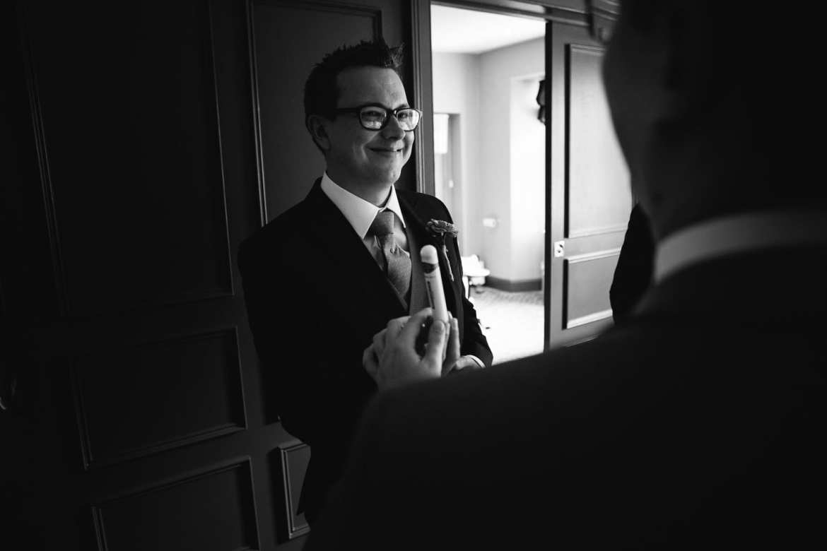 Black and white image of groom's friend supplying him with cigar