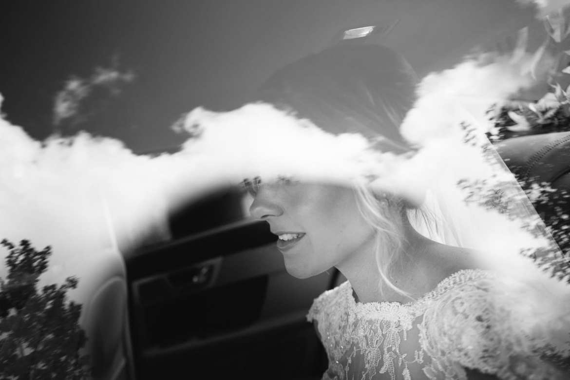 Black and white image of bride through car window