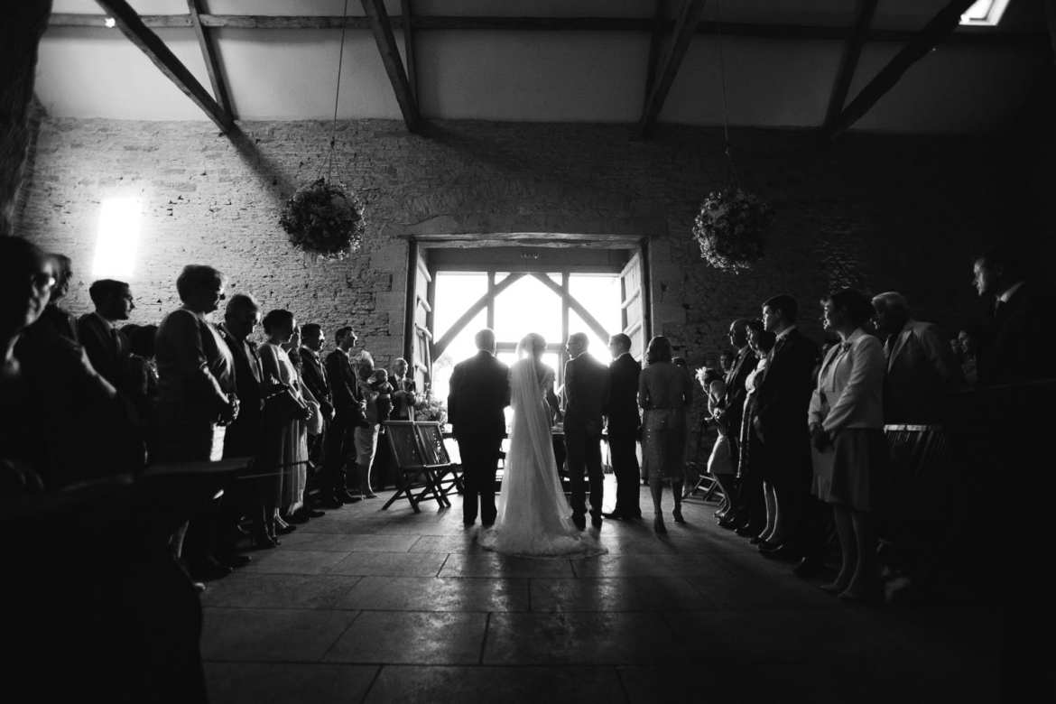 Black and white full length image of couple and ceremony