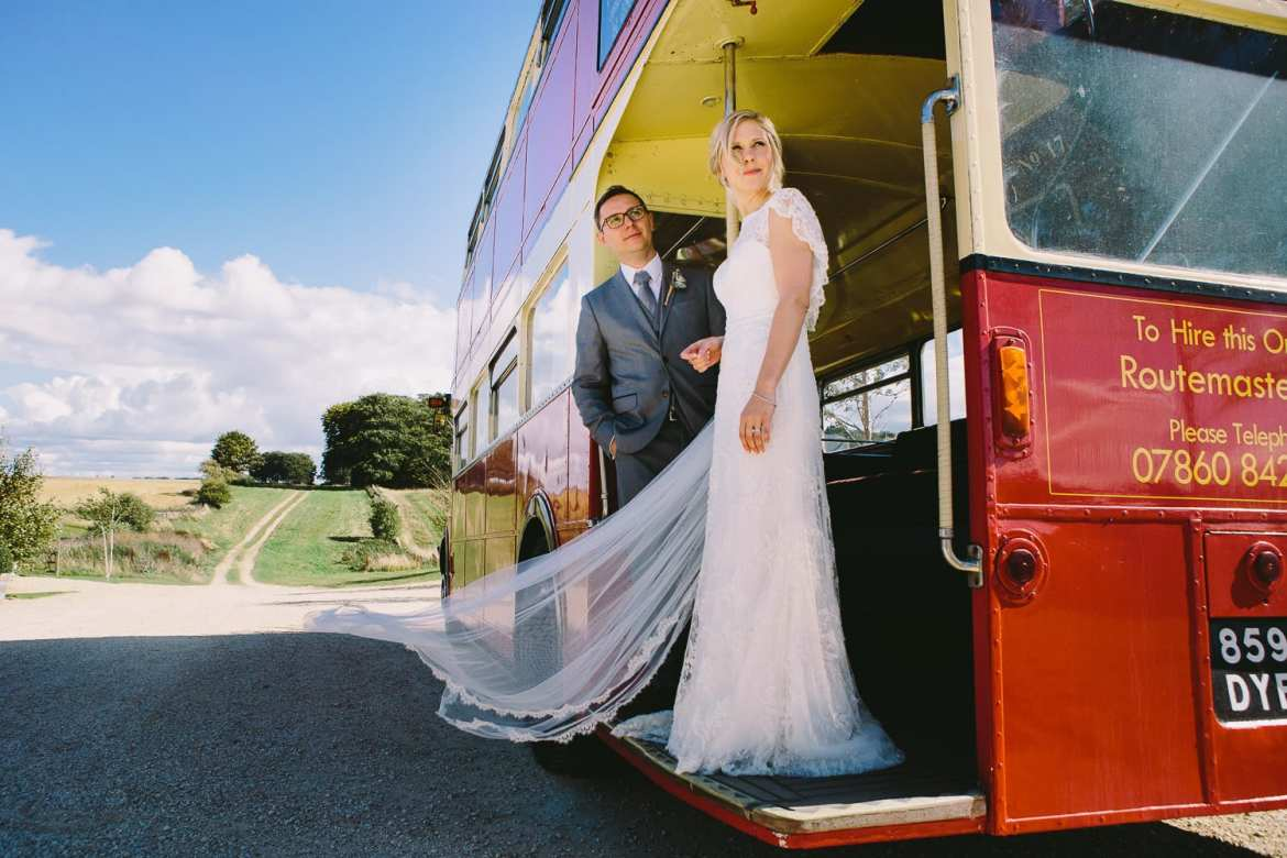 Couple standing on the vintage bus outside venue