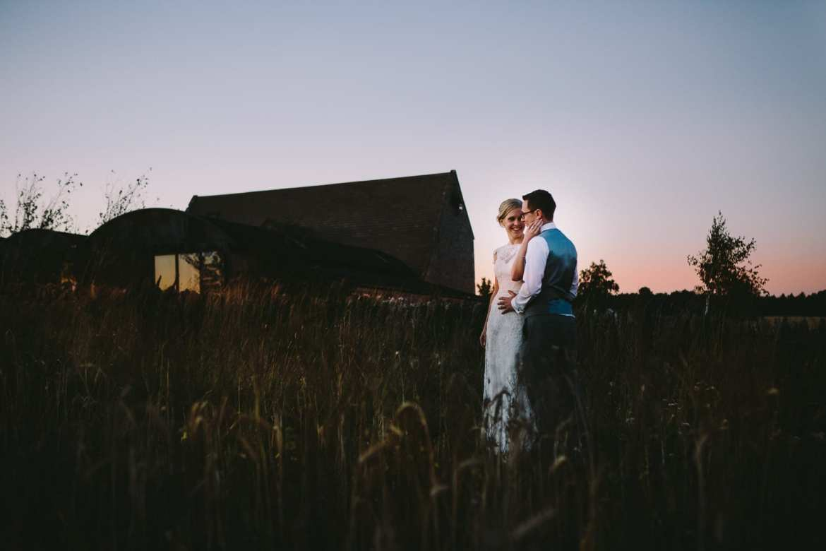 Sunset image of bride and groom standing in the field next to venue