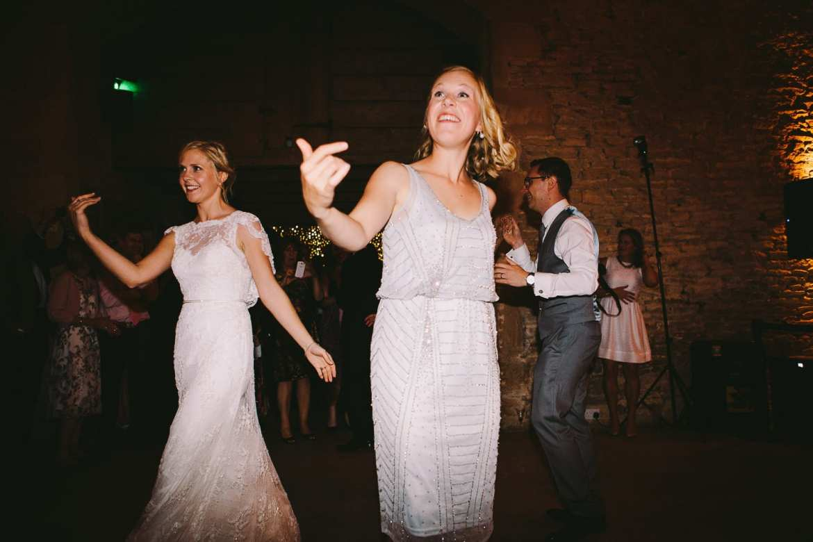Bride and bridesmaid beckoning guests onto dance floor