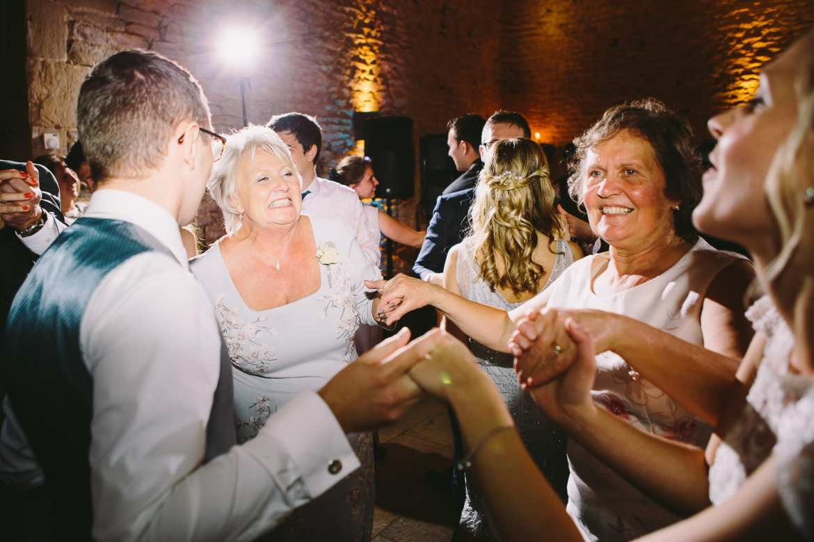 Bride and groom dancing with both mothers
