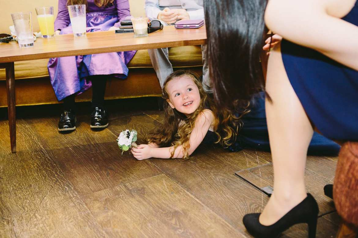 Flower girl playing under table at reception