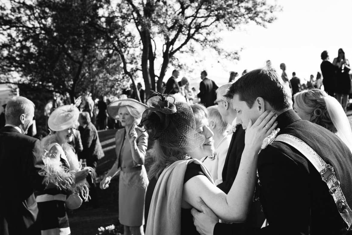 Black and white image of couple being greeted by guests at reception