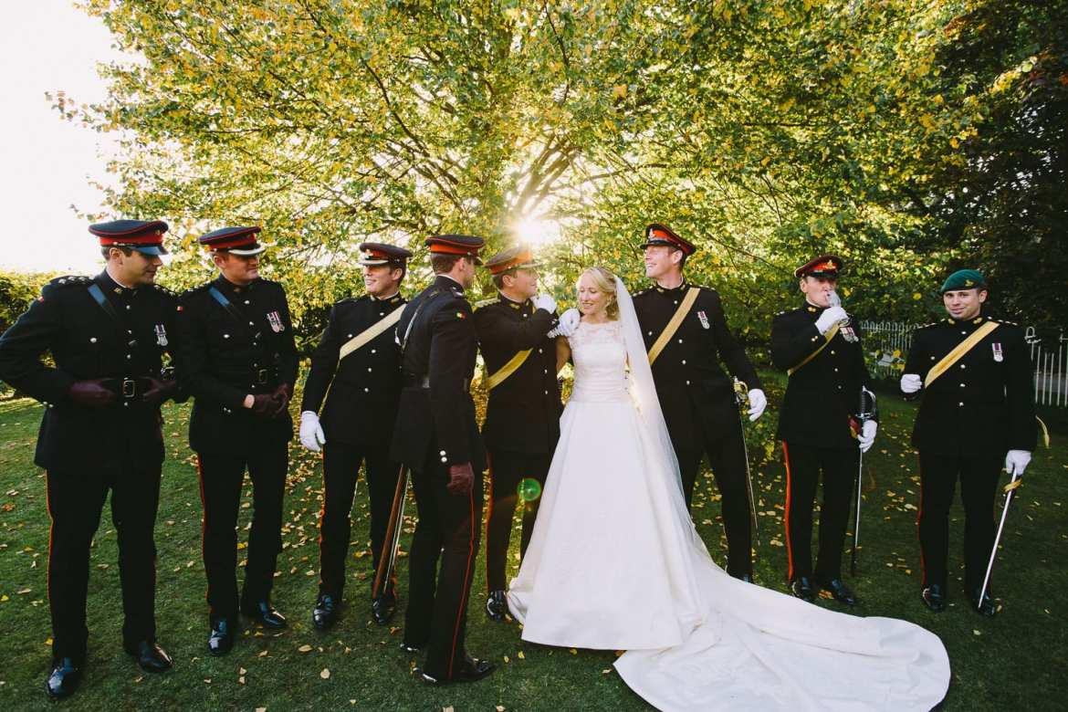 Bride and groom getting ready for group shot with military honour guard