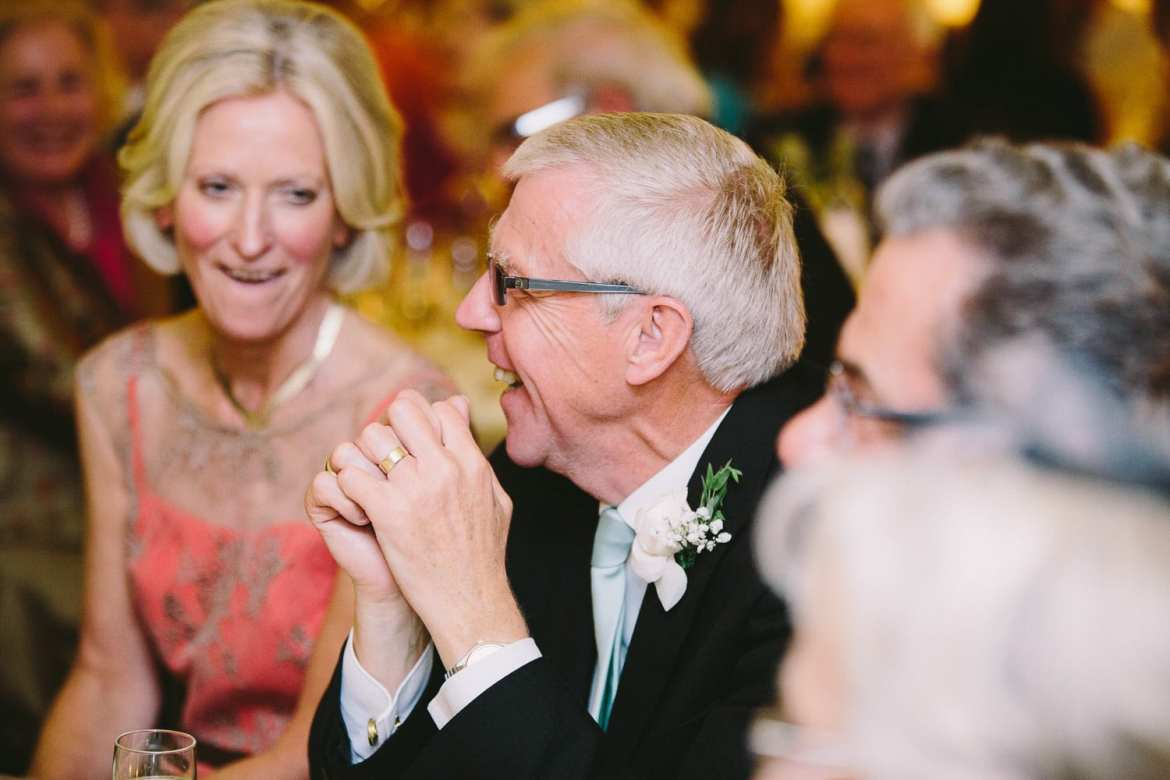 Grooms father laughing during speeches