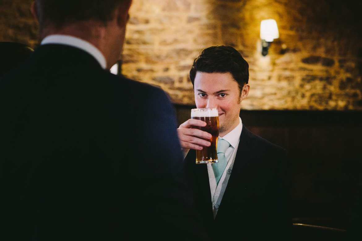 The groom having a pint in the pub before the wedding