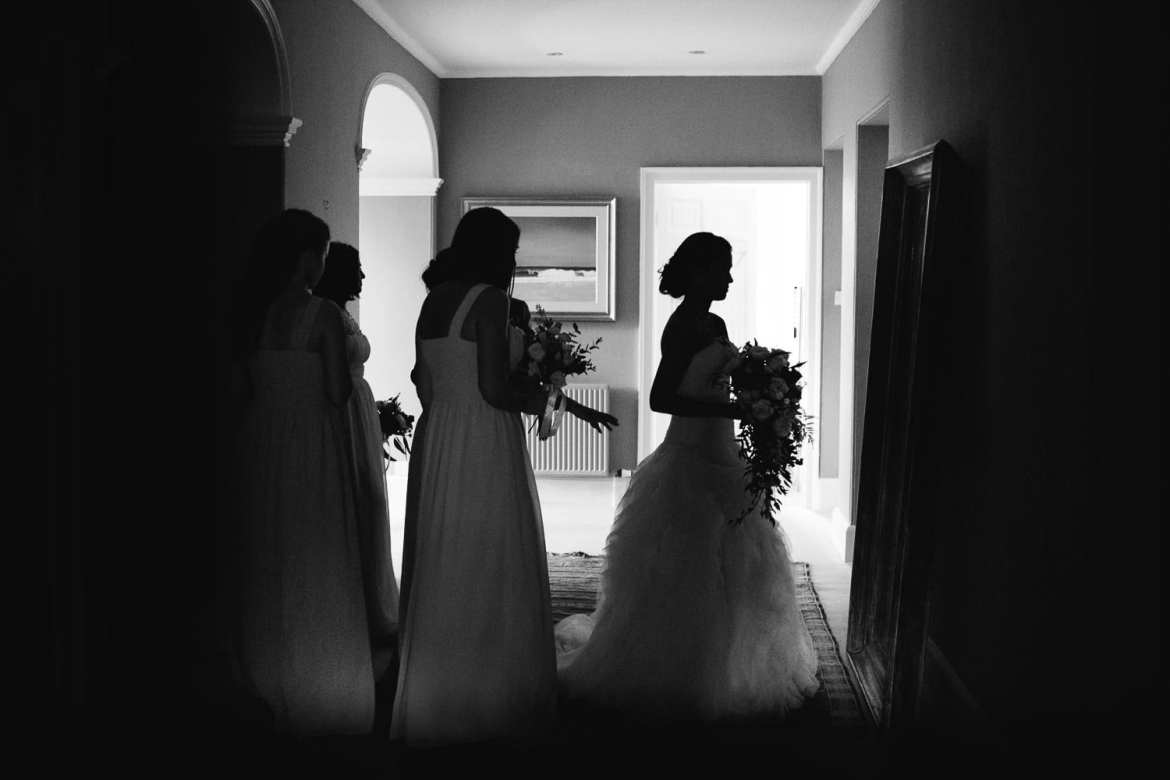 A black and white silhouette of the bride and bridesmaids