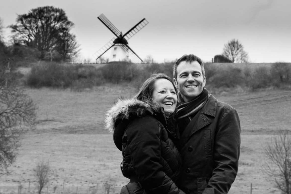 A laughing couple stand infront of cobstone windmill