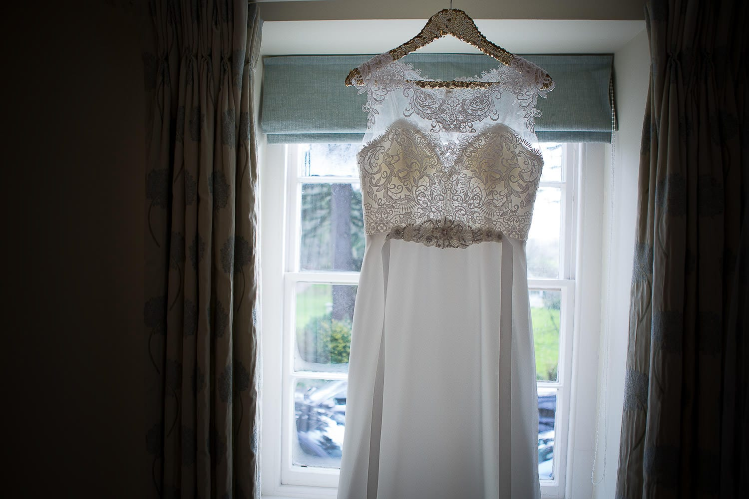 A Mori Lee wedding dress hanging in the window