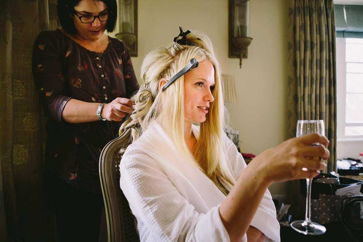 The bride with a glass of champagne having her hair done