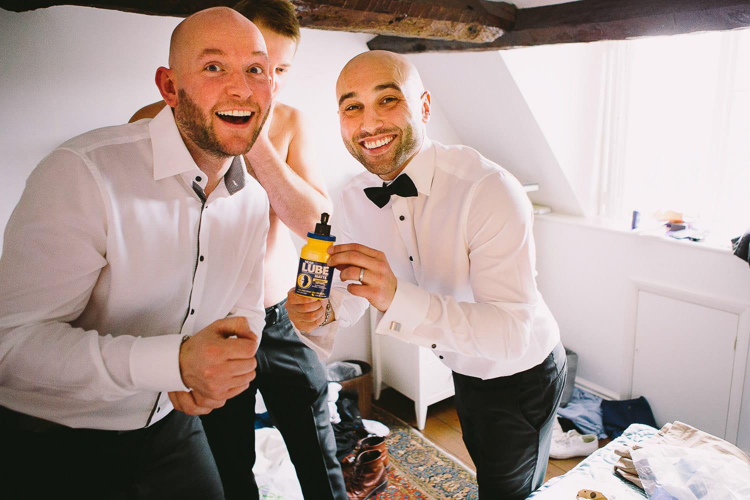 Some bald ushers holding a bottle of head lube