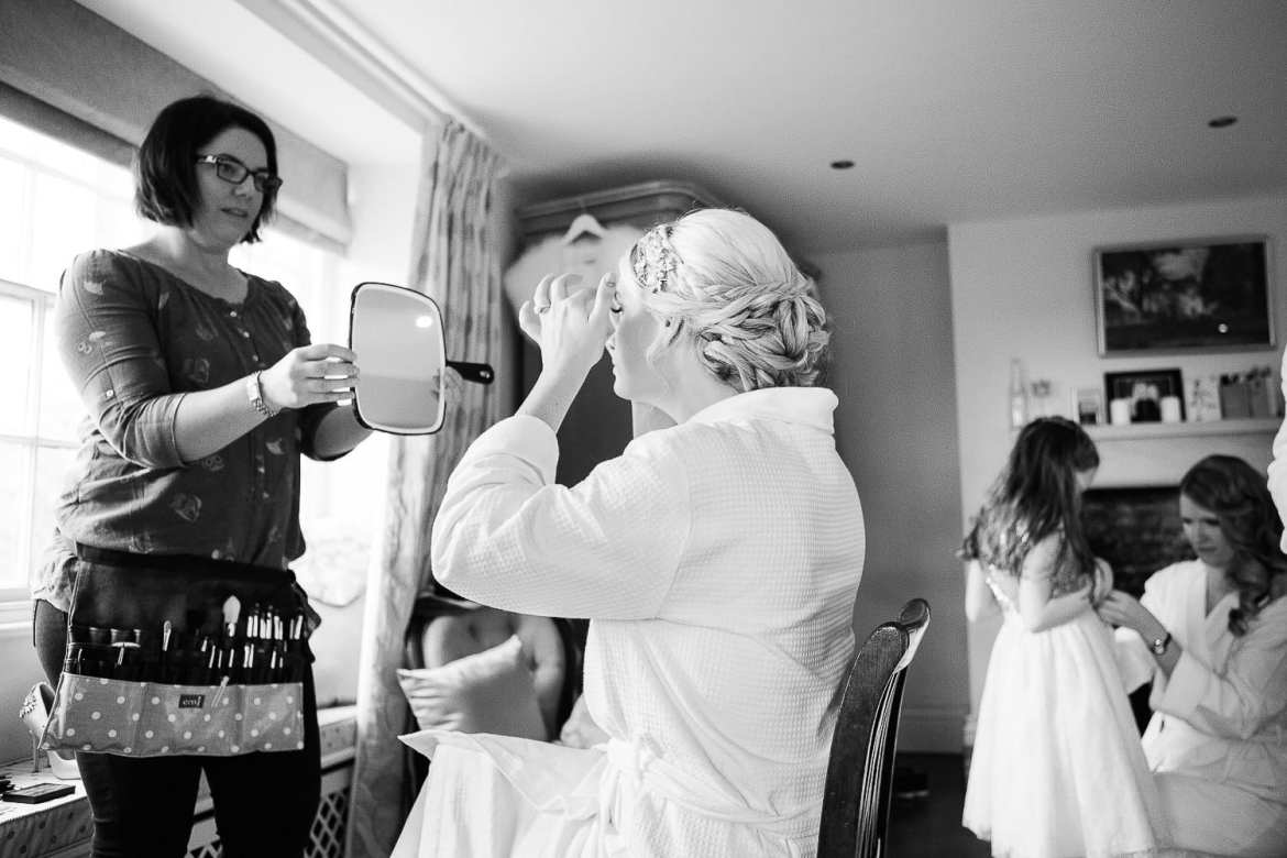 a back and white picture of a bride looking in the mirror