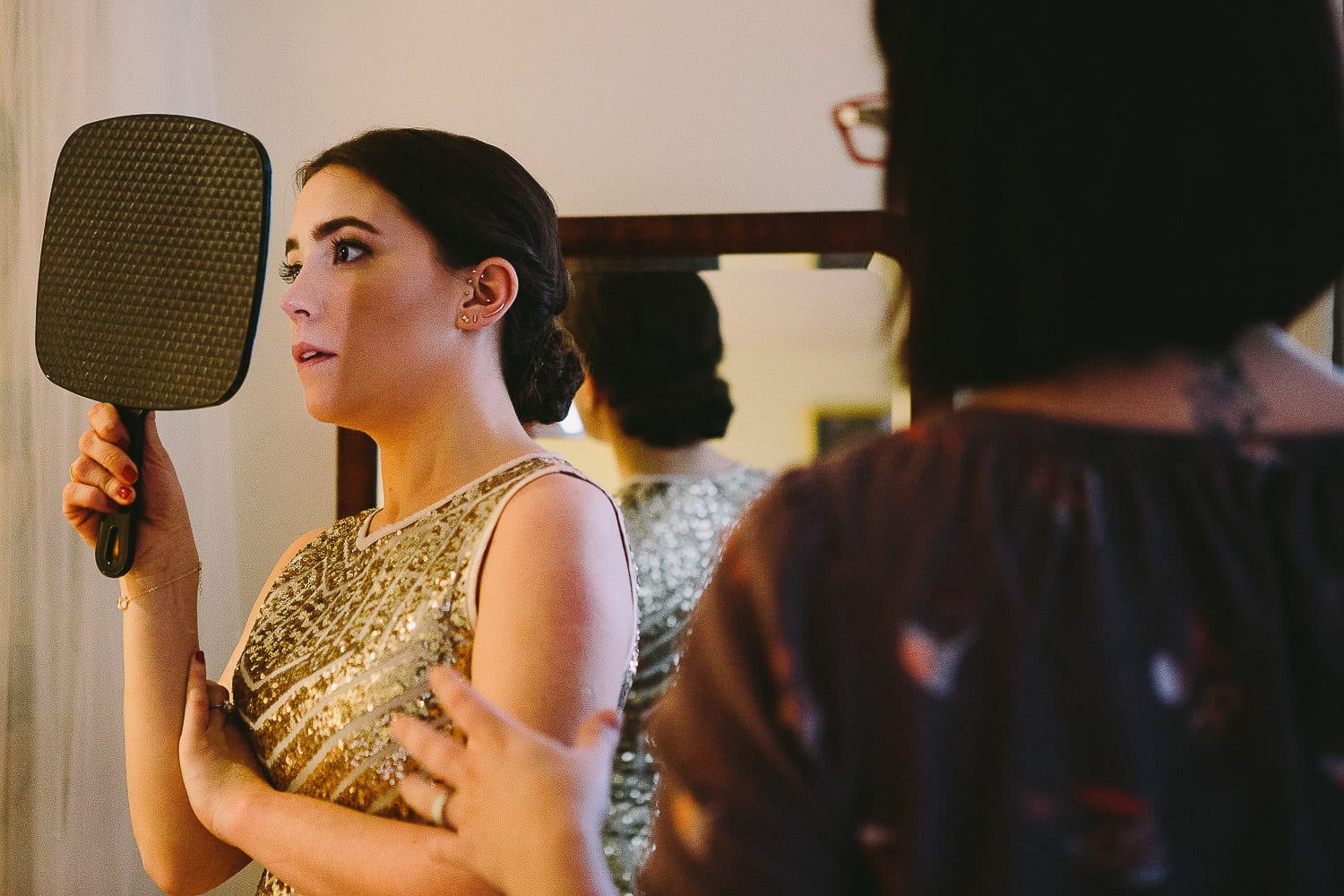 a bridesmaid checking her hair in the mirror