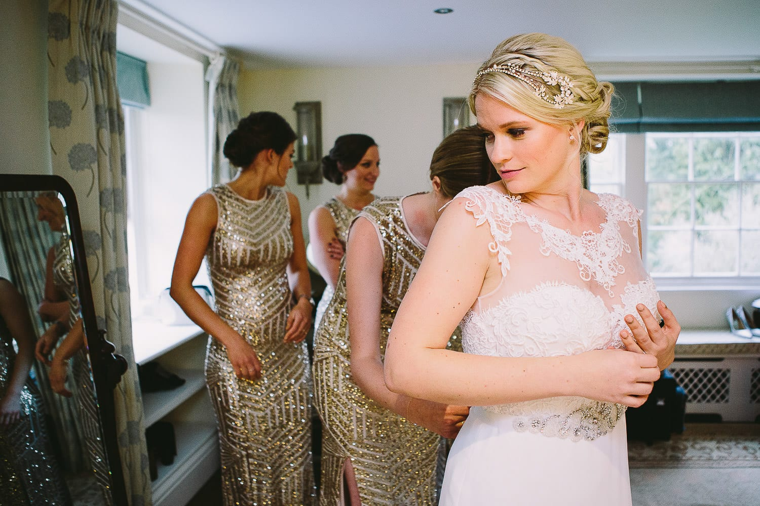 the bride checks her dress in the mirror