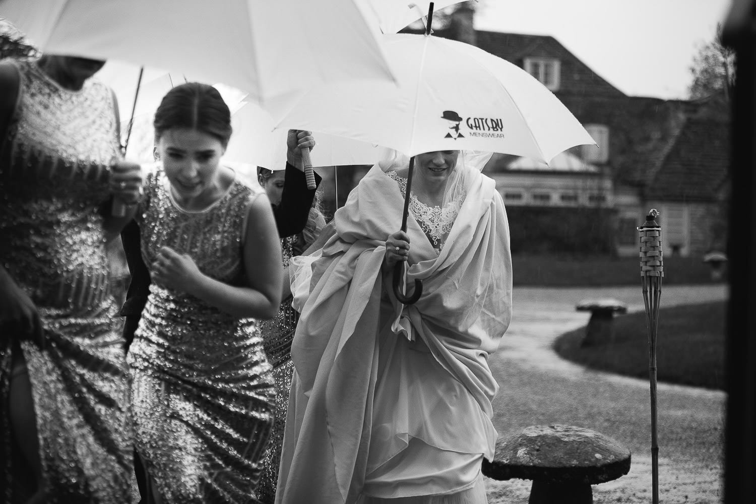 the bride arrives for the ceremony under an umbrella