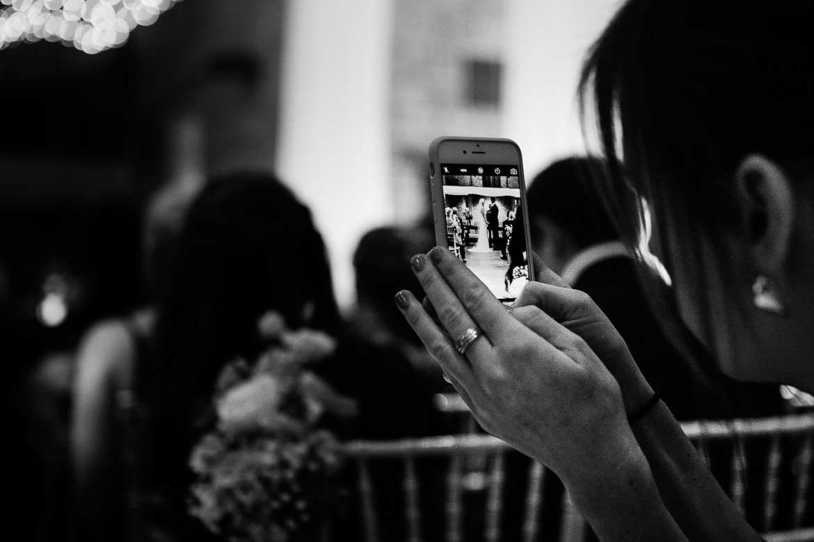 Close up image of guests phone taking a picture of bride and groom