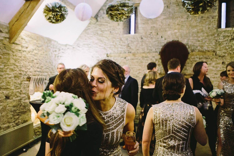 Bridesmaid kissing a guest