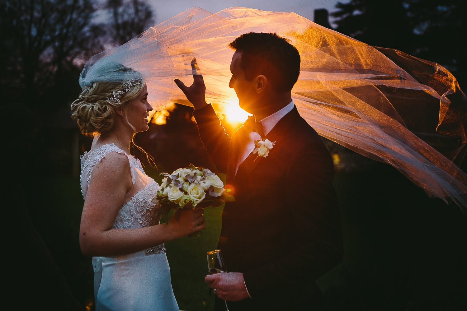 Sunset image of couple with bride's veil blowing in the wind