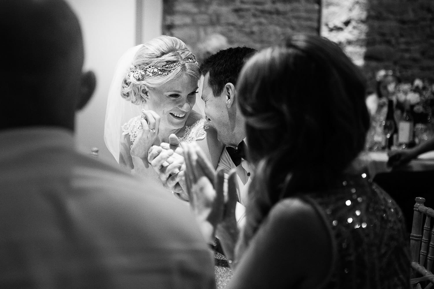 Black and white image of bride and groom laughing during speeches