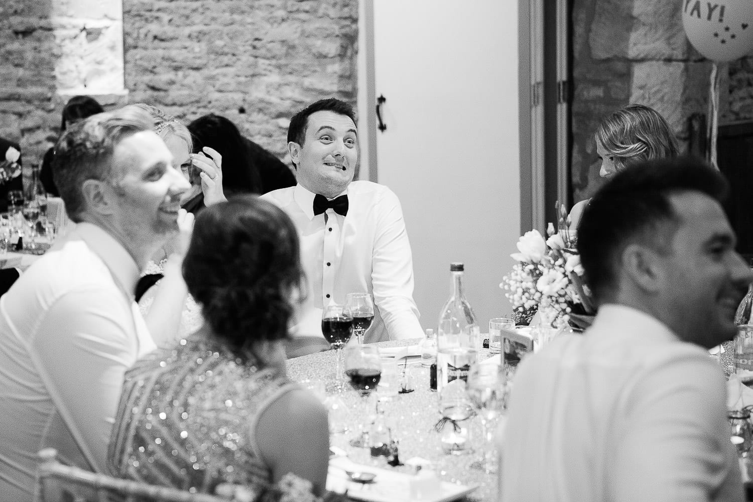 Black and white image of groom pulling a face during speech