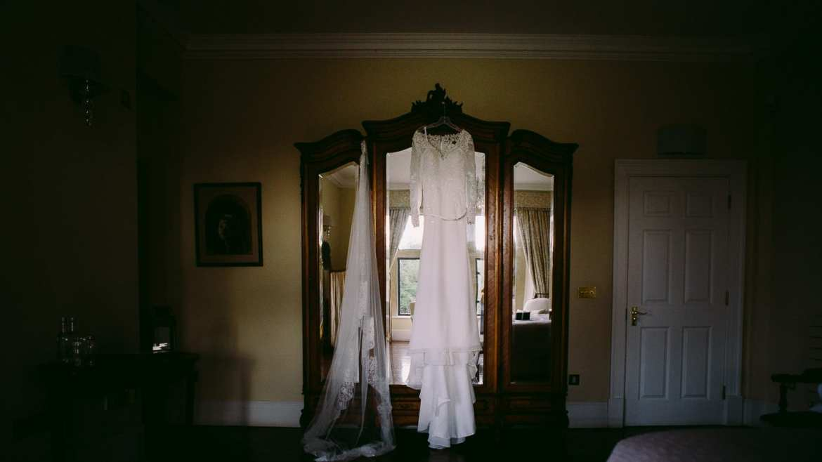 A wedding dress hanging on the wardrobe
