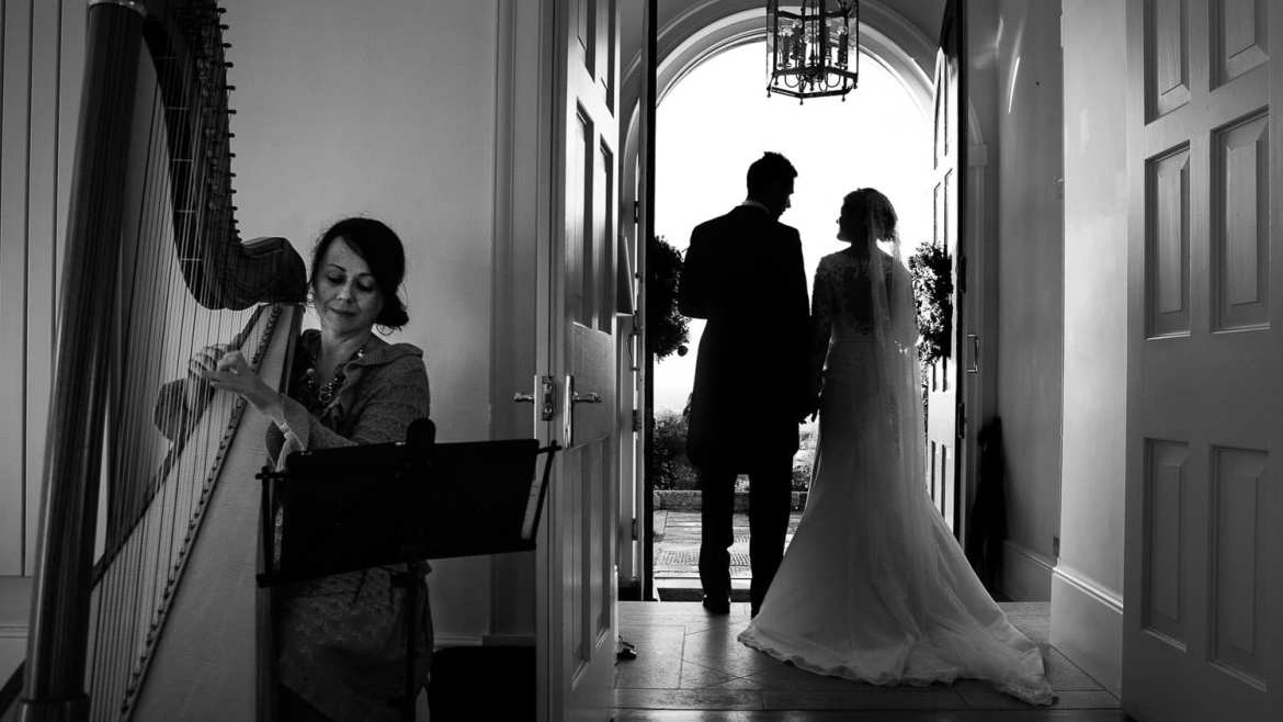 A harpist plays as the bride and groom stand in the doorway at Old Down Manor