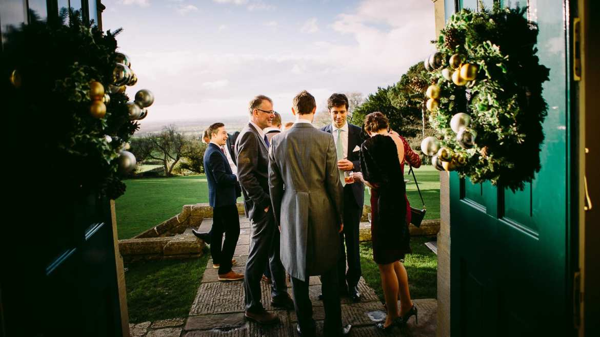 The groom chats to some wedding guests in the garden