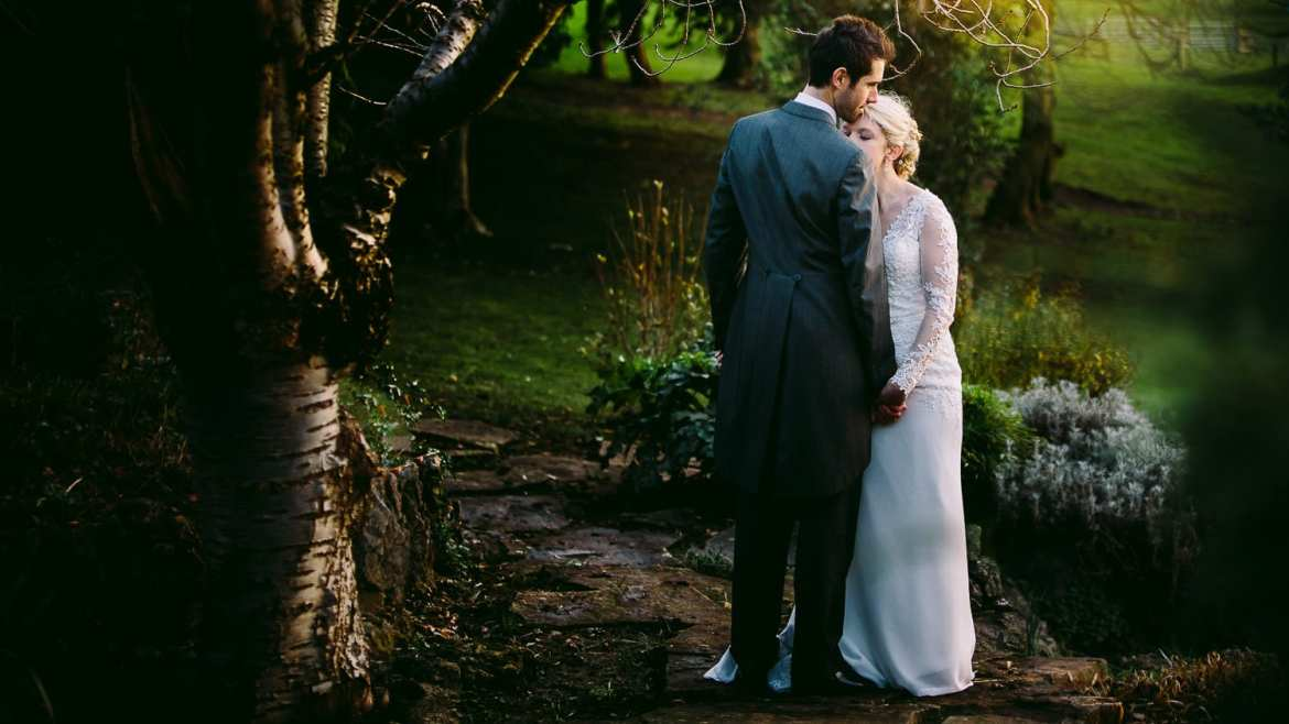 A portrait of the bride and groom under a tree