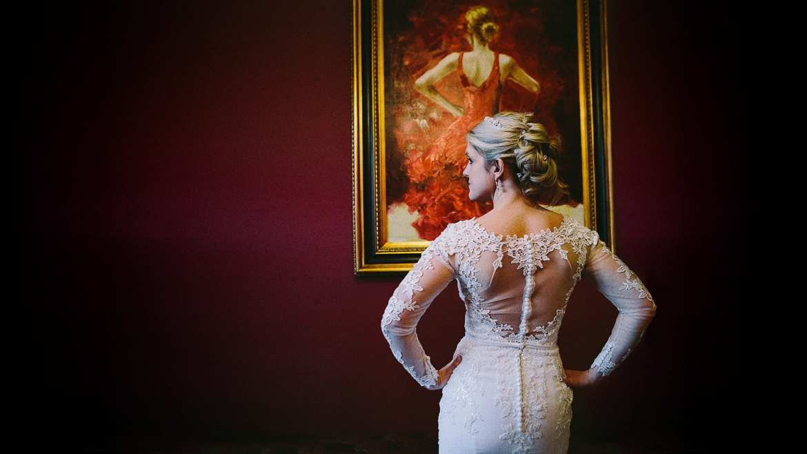 A portrait of a bride mirroring a painting on the wall in front of her