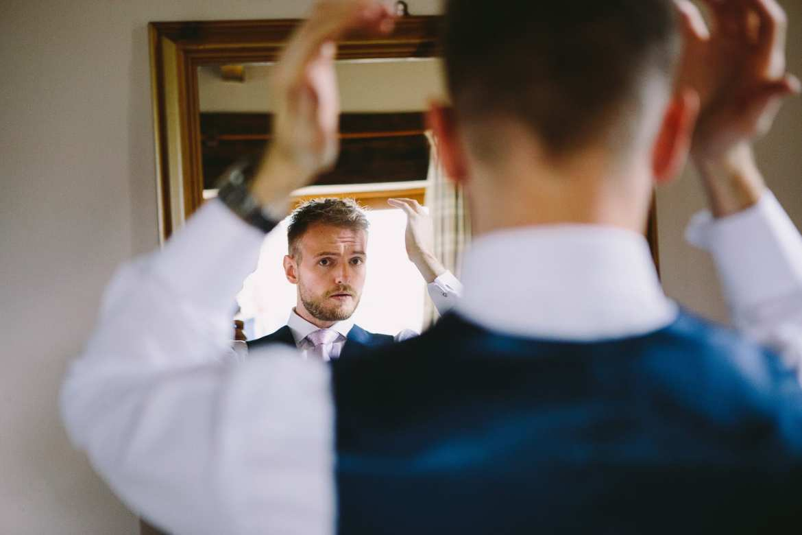 The groom adjusts his hair in the mirror