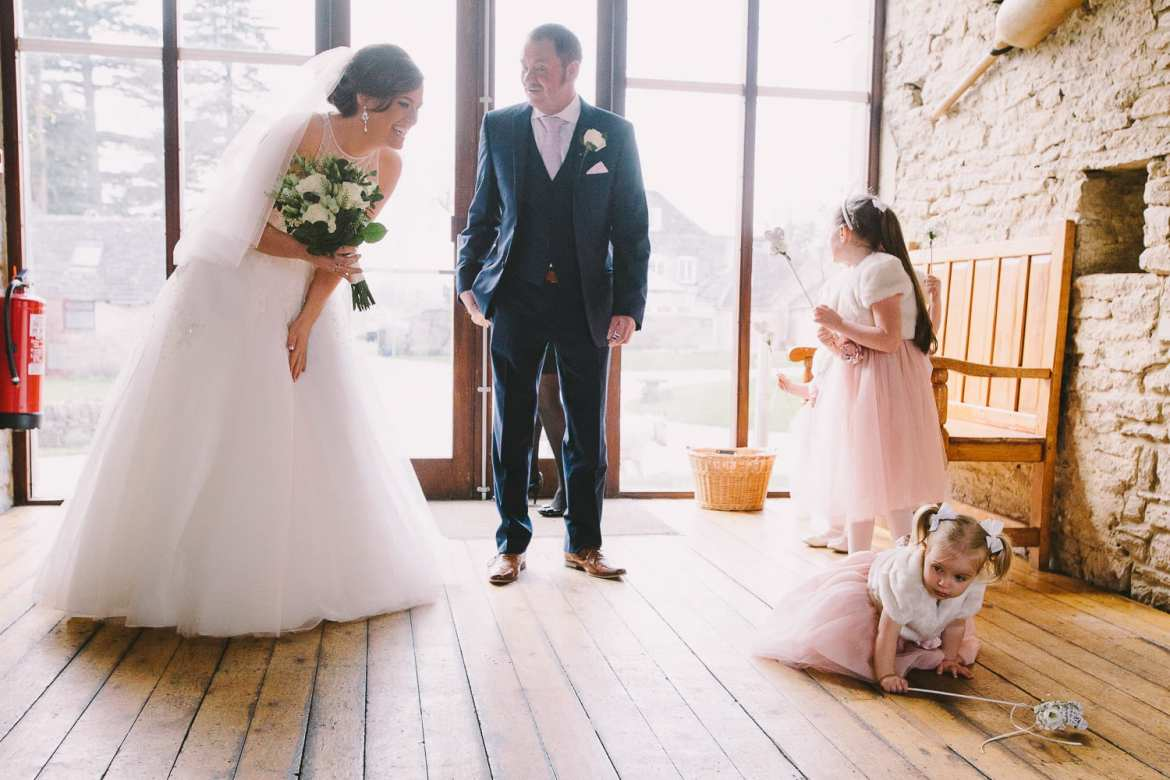 One of the flower girls is having a tantrum on the floor while the bride tries to calm her