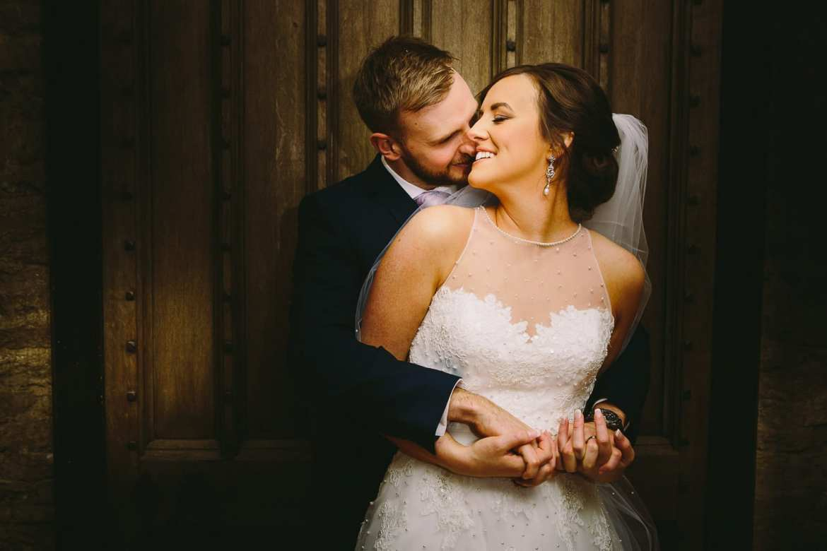 A portrait of the bride and groom in front of an old door