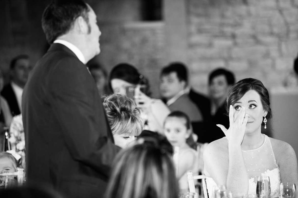 The bride wipes away tears during her father's speech