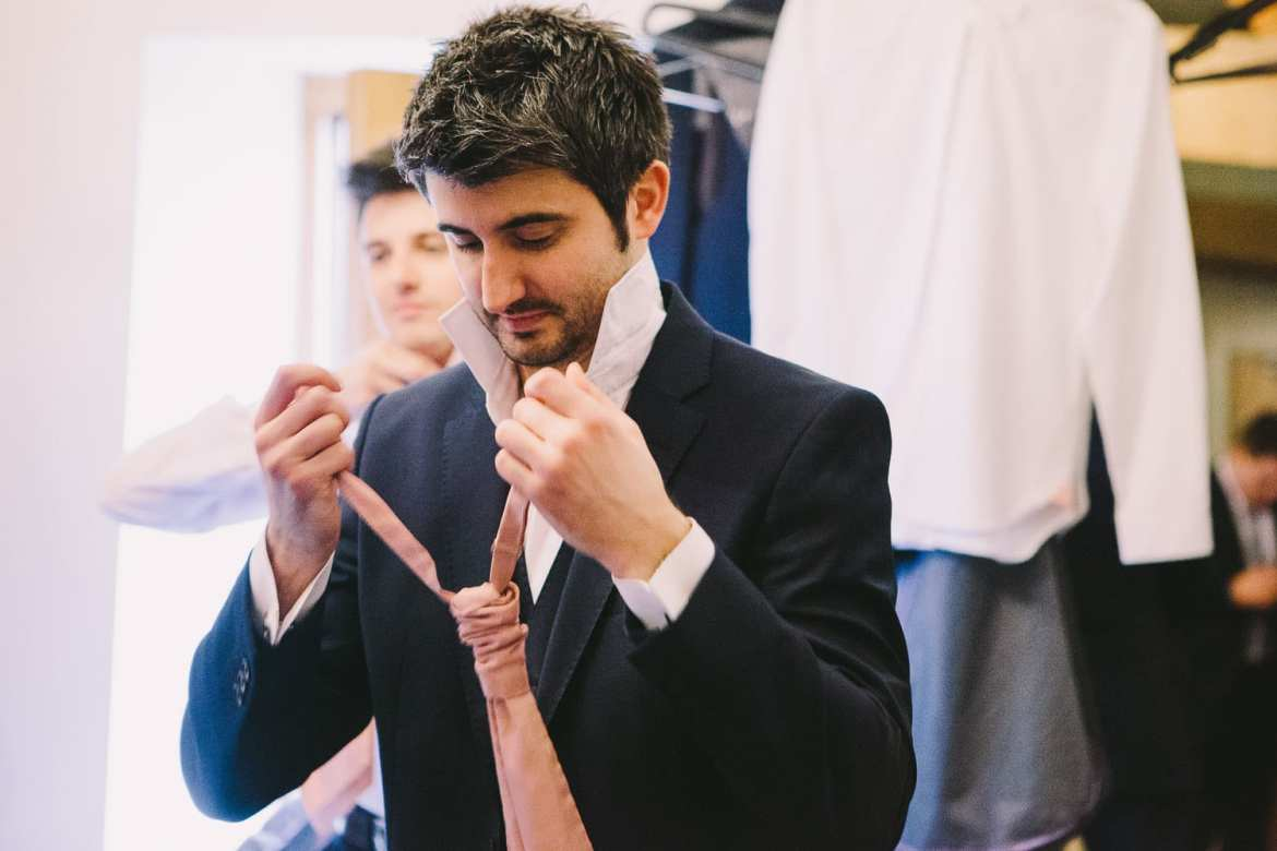 The groom putting his tie on