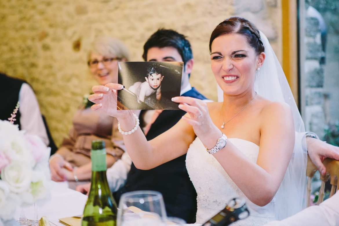 The bride is pulling a face as she holds up a picture of the groom as a baby